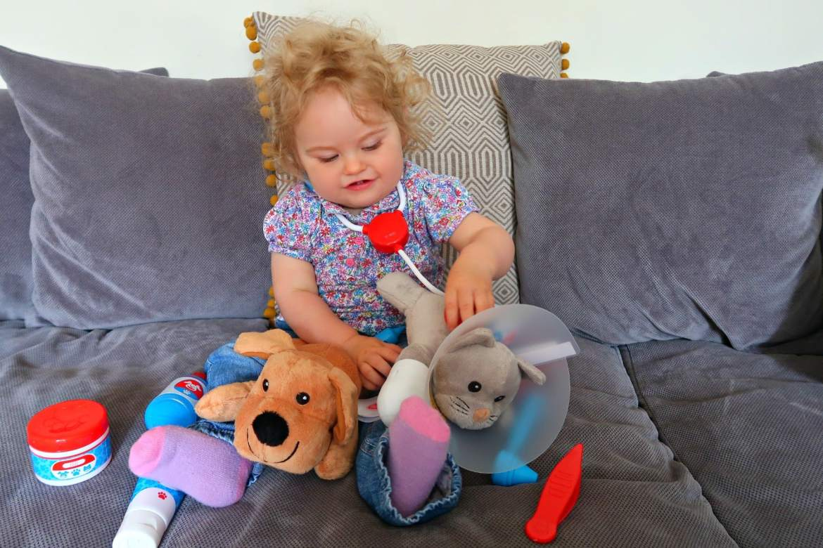 Melissa and Doug vet set being played with my baby girl on a grey sofa for ideas of activities to do with a toddler