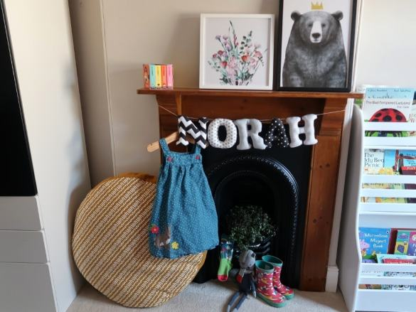 Frugi dress hanging on little wooden hanger on black fireplace in a little girls room