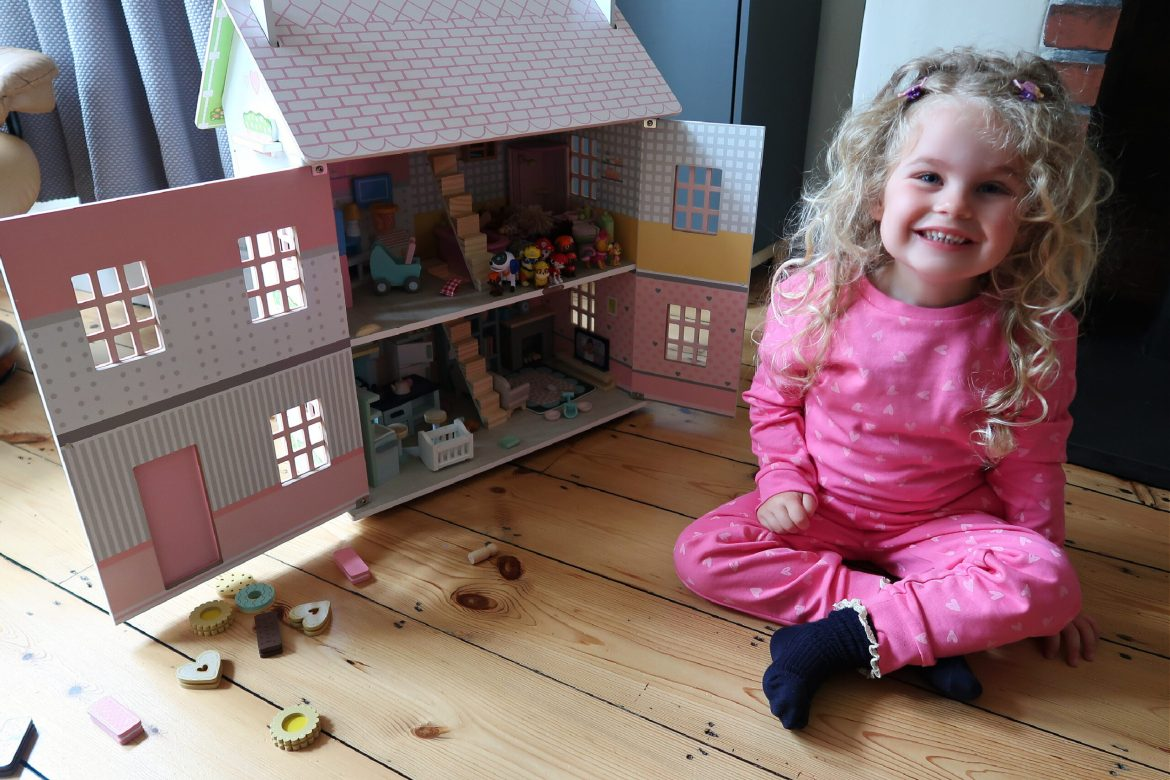 Little girl sitting by a dolls house wearing a pink outfit from Boots Uk
