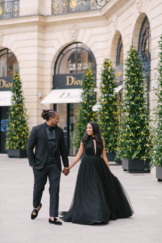 Cute couple walking holding in hands in front of Dior store in Place Vendome - beautiful Christmas decoration in the background