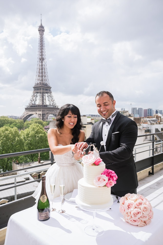Paris elopement - Bride and groom cutting wedding cake on Shangri La terrace with Eiffel Tower in the background - Planned by Rendez-Vous in Paris