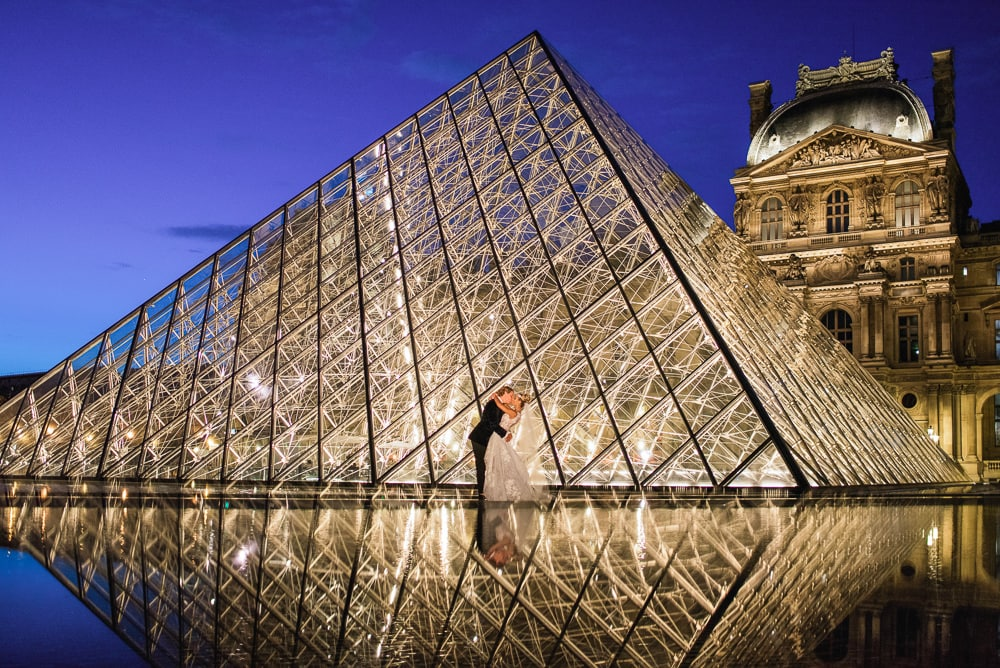 Paris elopement photographer - Creative reflection of bride and groom at the Louvre Museum Pyramid