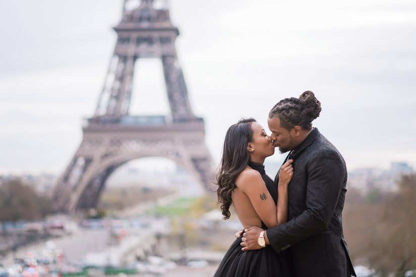 Young couple having a romantic kiss in Paris in front of the Eiffel Tower