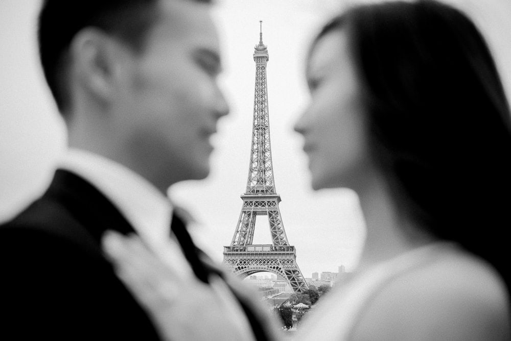Paris pre wedding photo - Asian bride and groom looking at each other and Eiffel Tower shows in between