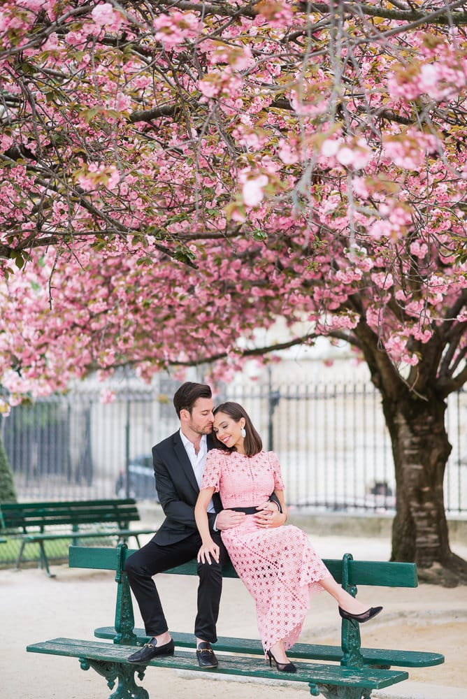 Spring engagement photos in Paris - Beautiful latina girl kissing her fiancé under a cherry blossom in Paris 2