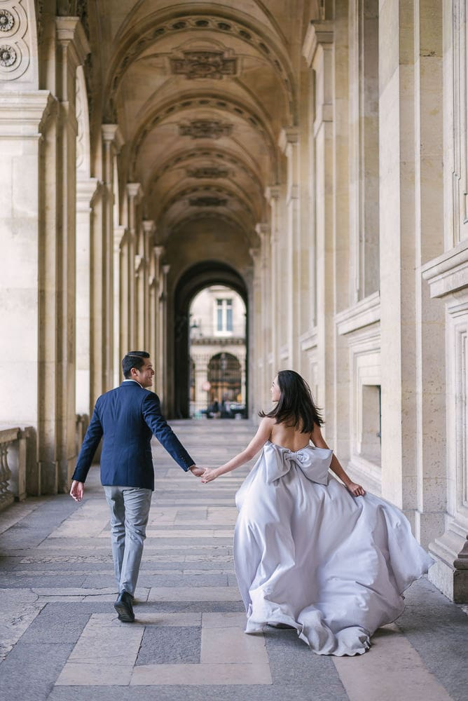 Paris engagement photographer - Asian couple running through the Louvre Museum elegant arches