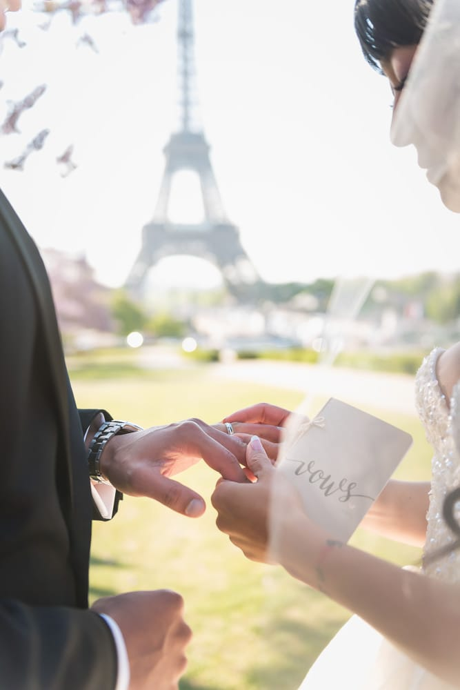 bride and groom exchanging wedding bands in paris