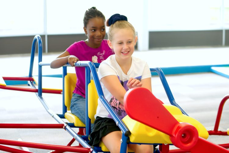 two girls are playing on an airplane riding toy