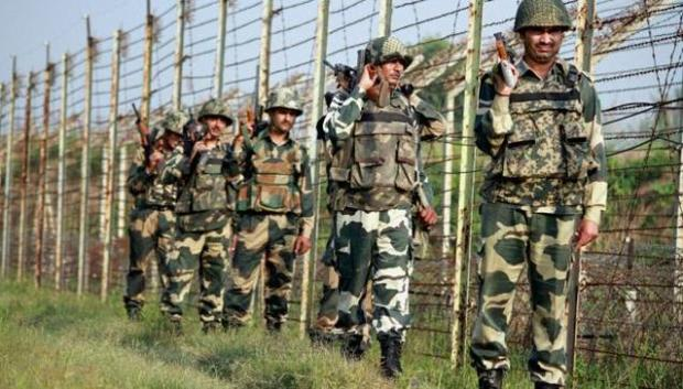 Border Security Force (BSF) personnel patrol along the fence at International Border in RS Pura Sector in Jammu on Wednesday. (PTI)