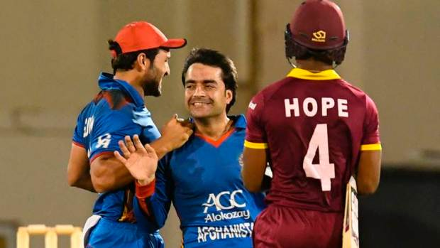 Rashid Khan (C) and Gulbadin Naib (L) of Afghanistan celebrate the dismissal of Shai Hope (R) of West Indies during the 1st ODI match between West Indies and Afghanistan at Darren Sammy National Cricket Stadium, Gros Islet, St. Lucia, June 09, 2017. / AFP PHOTO / Randy Brooks