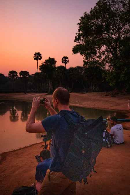 Nate taking a photo at sunrise with few people around him