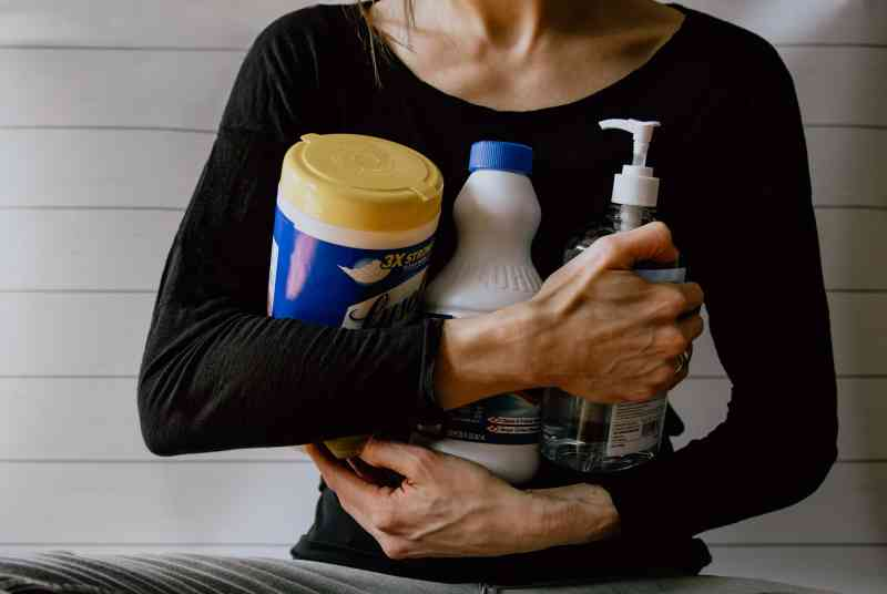 Lady holding cleaning supplies