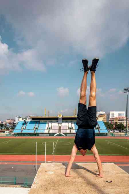 Nate doing handstand at National Olympic Stadium in Phnom Penh
