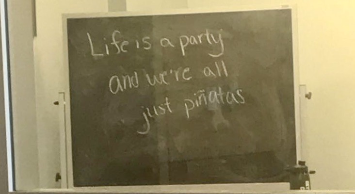 """A student writing on a chalk board in a study room of the Science Center on Gettysburg College's campus. It reads """"Life is a party and we're all just piñatas."""""""