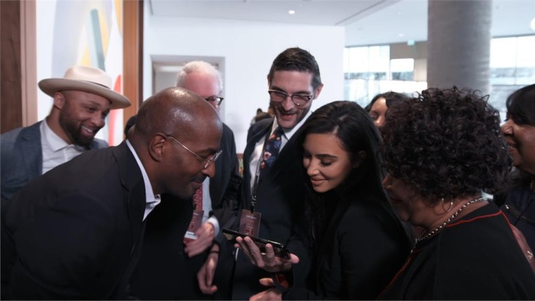 Van Jones, Kim Kardashian, Alice Johnson, Louis L. Reed and Alex Guditch of #cut50 huddle over a cell phone to watch president Trump