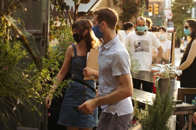 Guests with masks on wander inside the PHS Pop-Up Garden on South Street