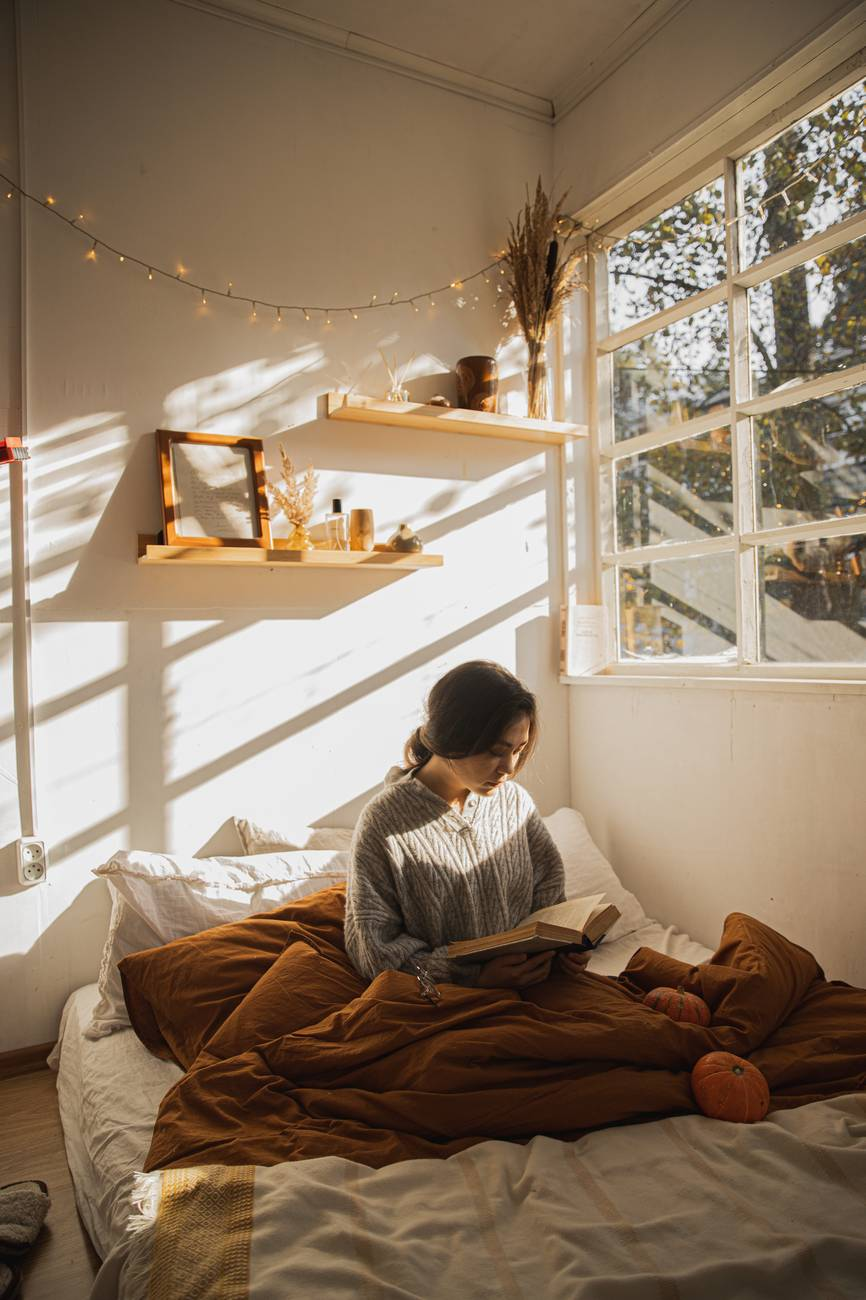 woman in gray long sleeve shirt sitting on her bed reading a book