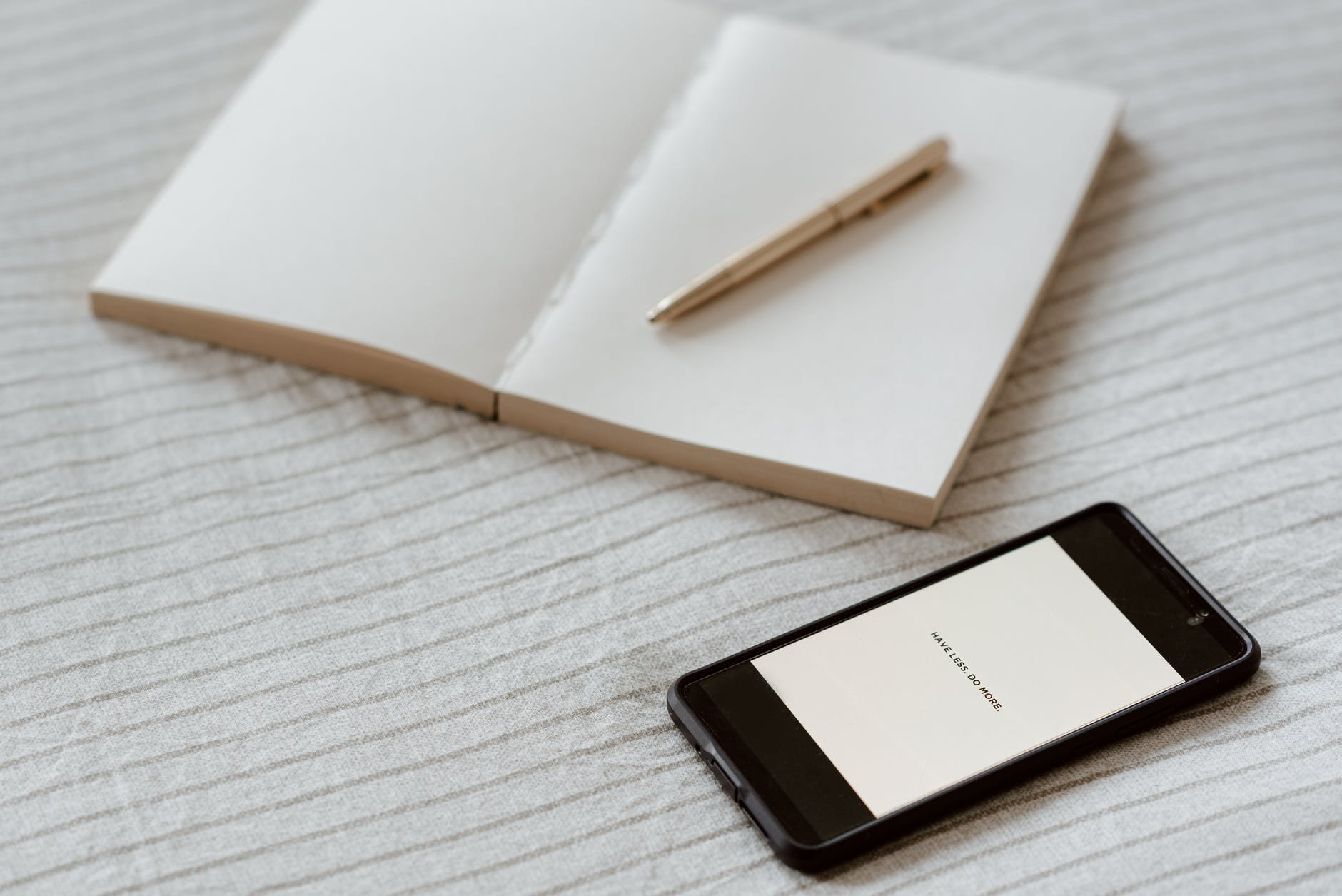 smartphone near empty notebook with pen on bed