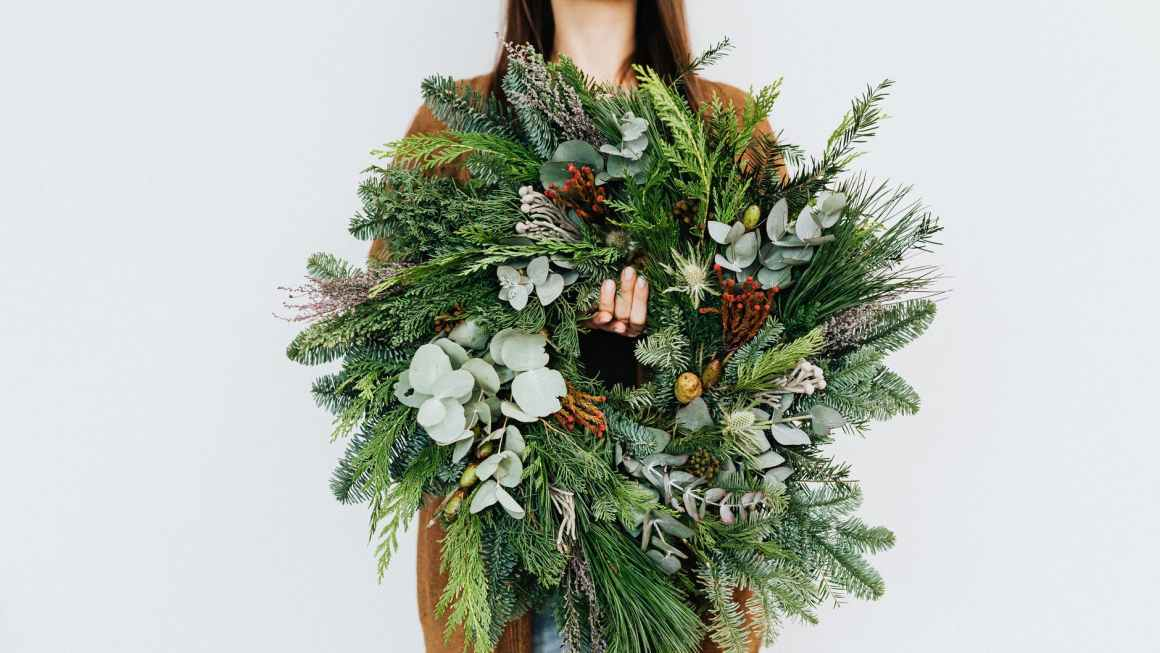 woman holding a christmas wreath decoration