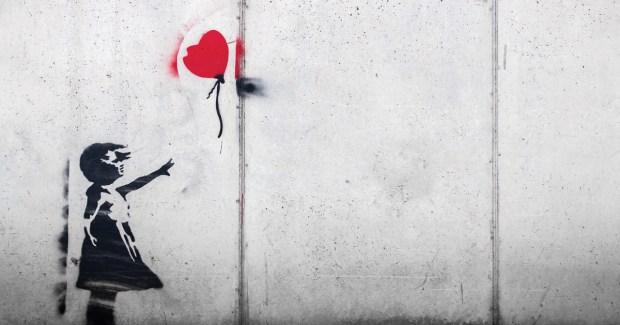 girl letting go of a heart balloon
