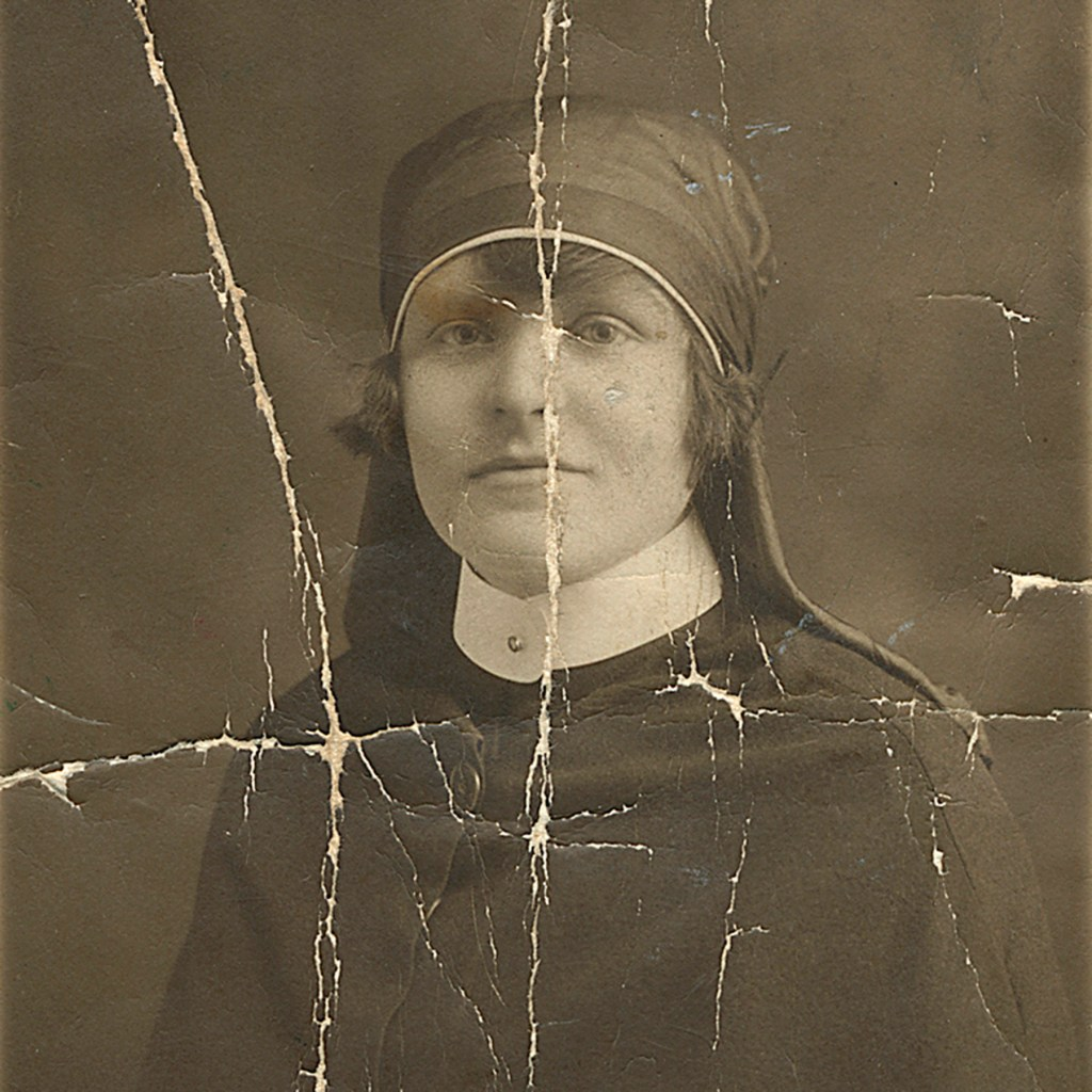 Old photo of a lady with a crack running through her face.