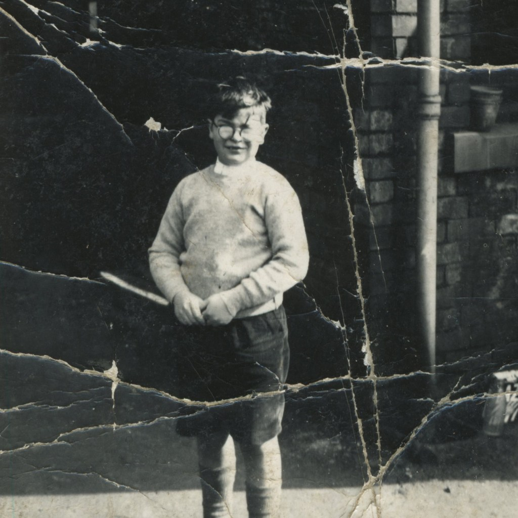 Photo of a young boy with cracks all over it.