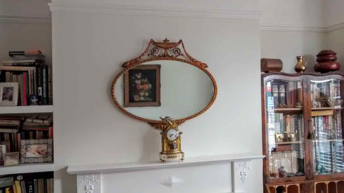 An Antique mirror hung on chimney breast