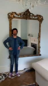 Patrick standing in front of large antique Rococo mirror hung in Bromley, Kent.