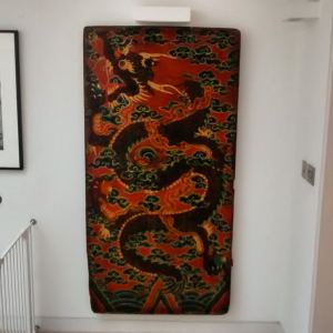 A red and black Tibetan door hung at the end of a hallway in Blackheath.