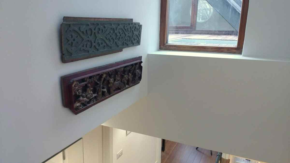 Antique wood carved panels hung above a stairwell in a home in Kemp Town. Perfectly positioned to be viewed both indoors, from the staircase, and outdoors from the roof terrace through the window.