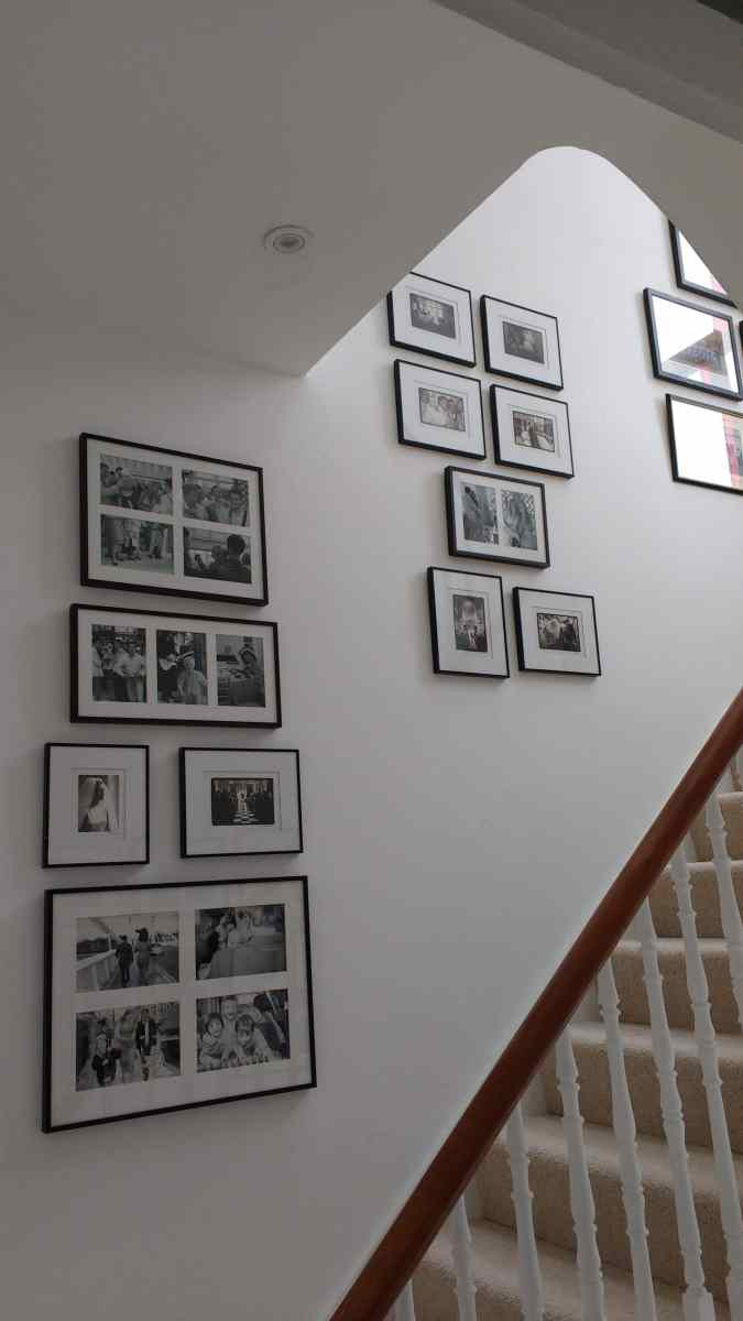 Three separate groupings of black and white photographs running above a staircase.