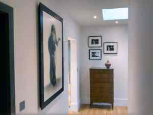 Black framed artwork hung in the upstairs corridor of a home in Horsham