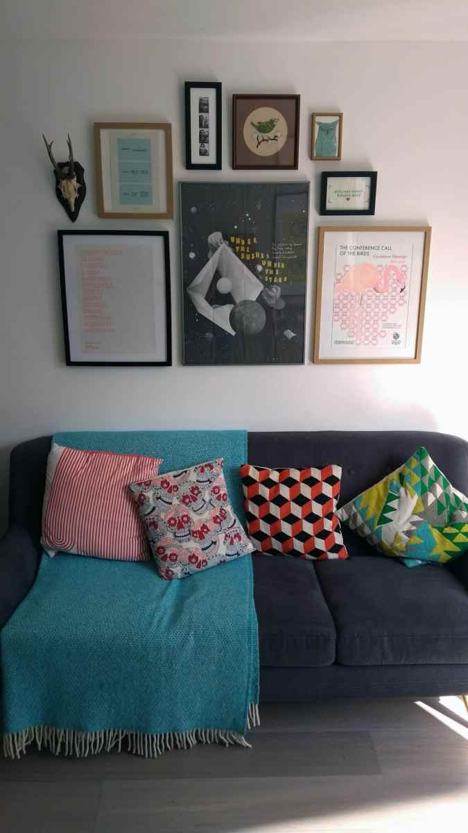 An eclectic collage wall of psters, prints and bones hanging above a sofa.