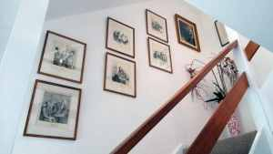 8 prints arranged in duos along a staircase in Enfield, London