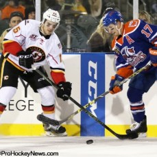 Kenny Agostino (15) and Andrew Miller (17) look to control the puck along the boards