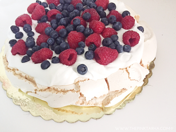Pavlova topped with raspberries and blueberries.