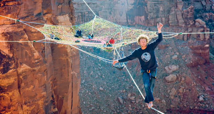 Base jumpers hand knit a spider web of highlines dangling