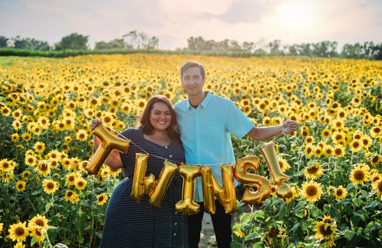 "Miranda & Kevin Schultz of The Plus Life Blog Announce Pregnancy With Twins Standing in Field of Sunflowers Holding Balloon Sign Reading ""TWINS"""
