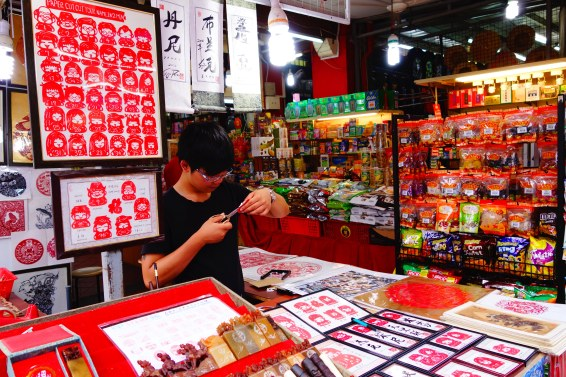 In the China Town market, a man cut out names and images from paper for souvenirs.