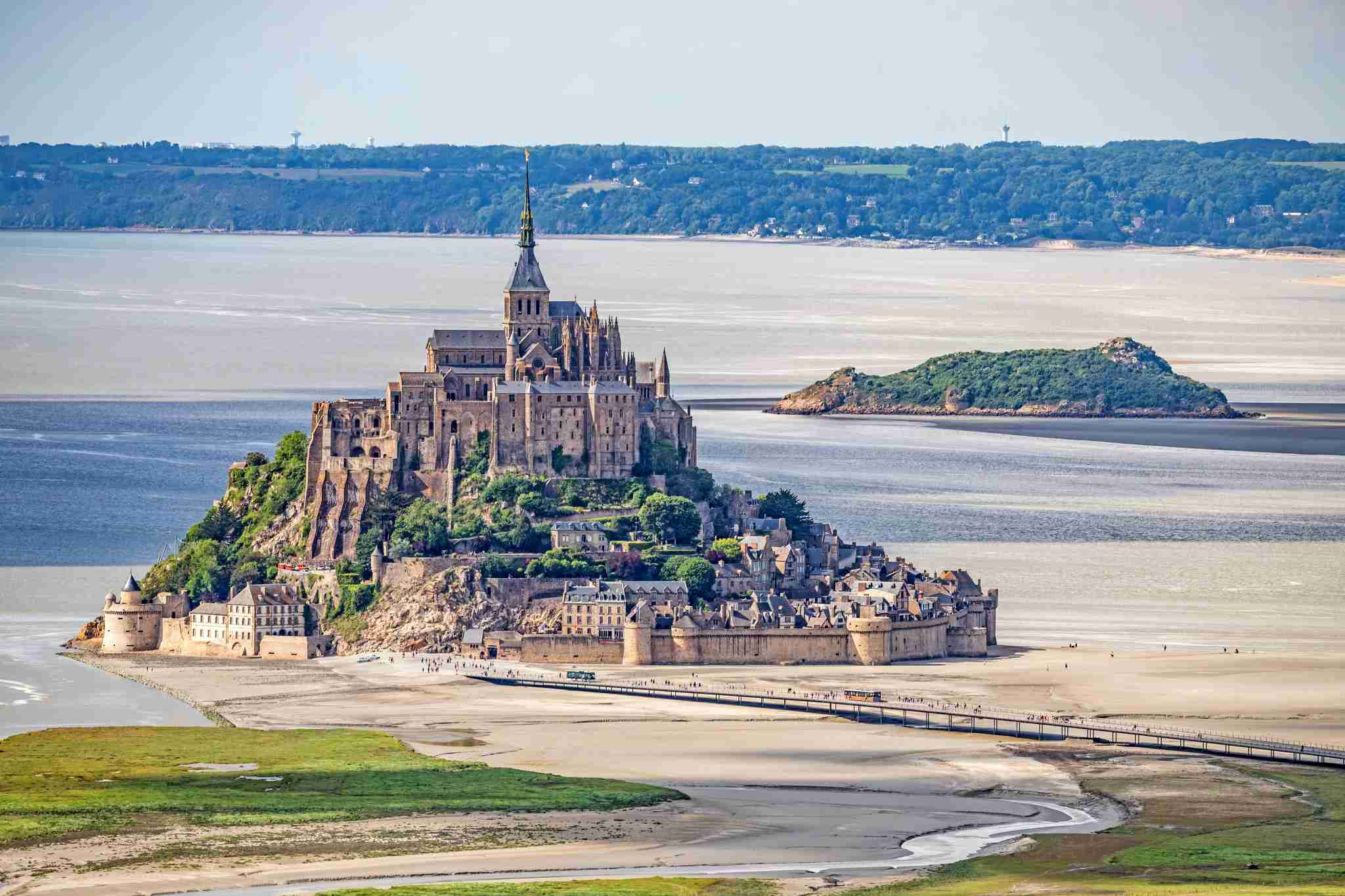 Aerial view of the Mont-Saint-Michel at low tide. In the background, the small island of Tombelaine. (Photo by: Andia/Universal Images Group via Getty Images)
