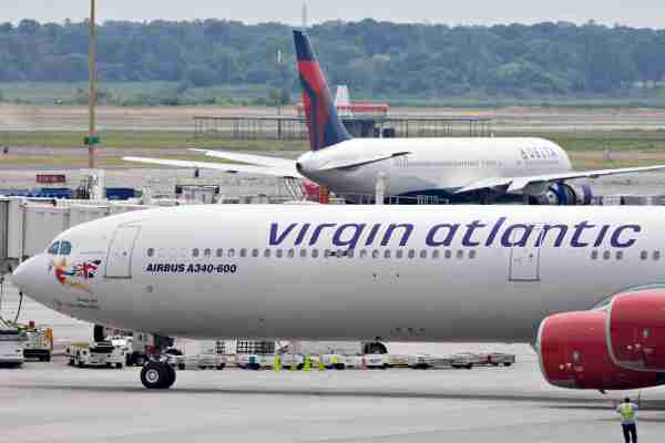 UNITED STATES - JULY 20: A Virgin Atlantic plane taxis past a Delta plane at John F. Kennedy International Airport in New York, U.S., on Monday, July 20, 2009. Virgin Atlantic Airways Ltd., the U.K. carrier owned by billionaire Richard Branson, will reduce seating capacity by 7 percent this winter and said it