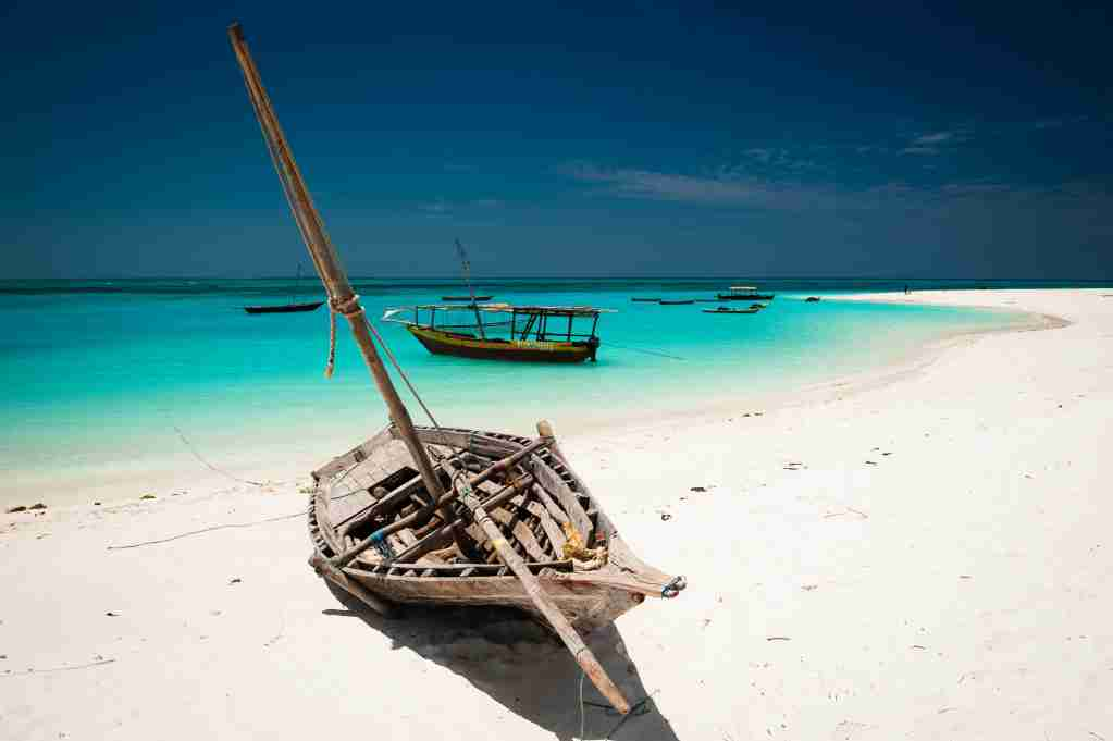 An old dhow lies on a Kendwa Beach with the turquoise waters of the Indian Ocean in the background, Zanzibar, Tanzania