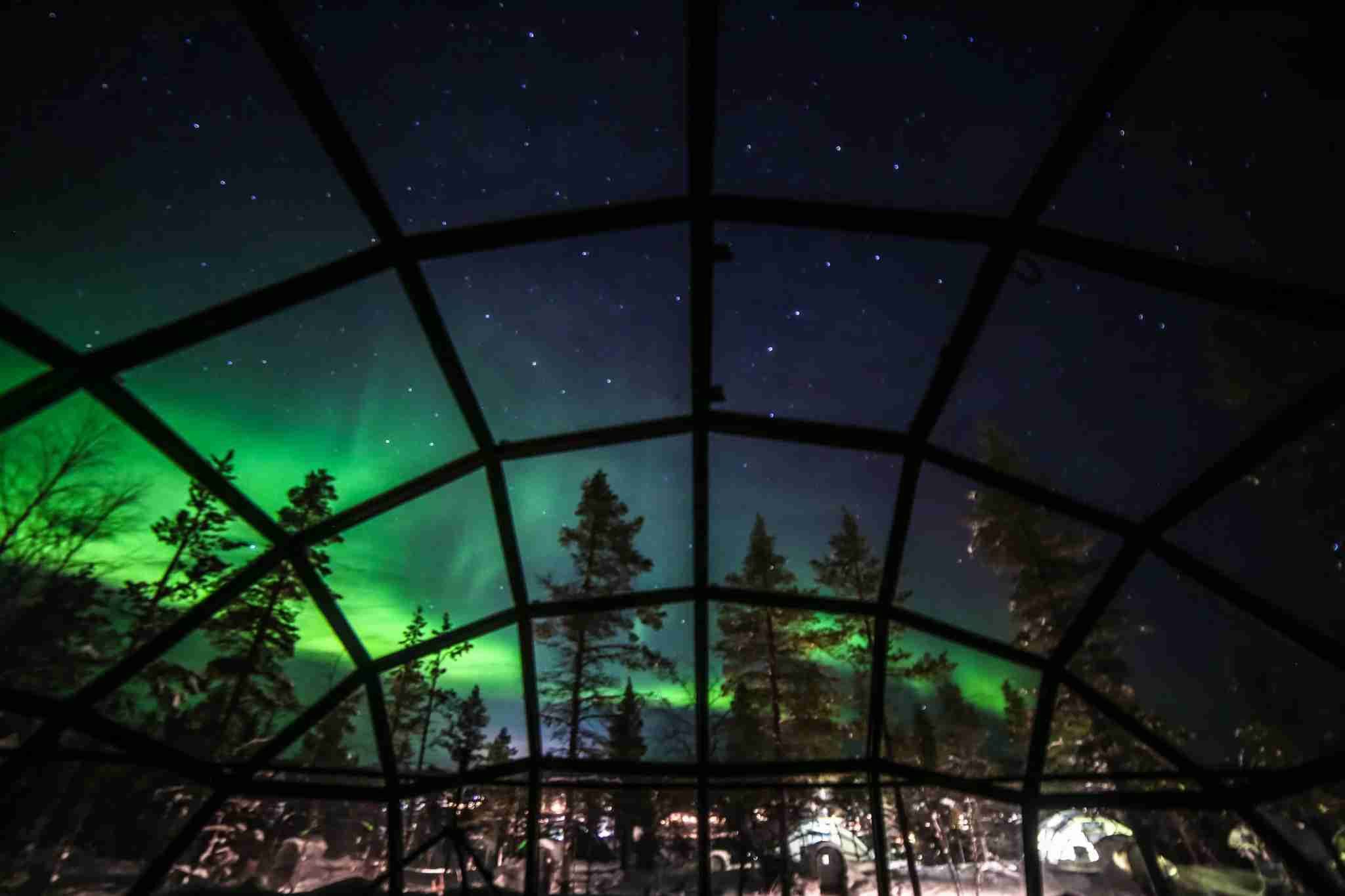 Helsinki, Finland - January 16, 2018: Aurora borealis, also known as Northern lights shining in the night sky seen from Glass Igloos, Kakslauttanen Arctic Resort West Village, Saariselkä, Lapland, Finland.