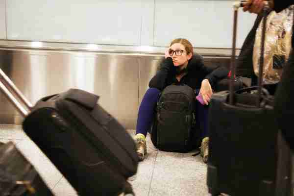 Distraught woman sits in airport while travelers pass her after realizing she forgot her passport.