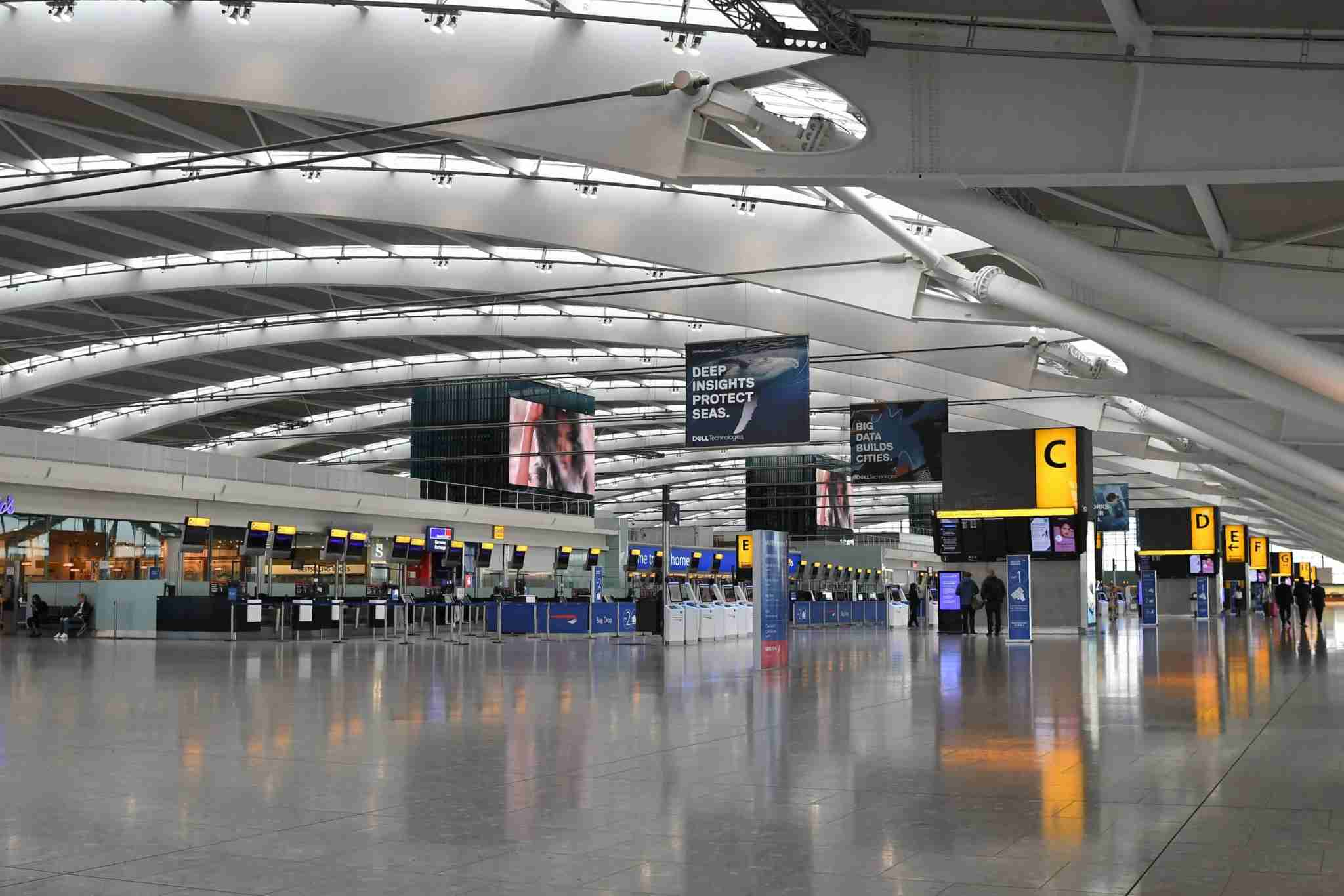 A few passengers walk around the near-deserted departure area at Heathrow airport Terminal 5 in west London on September 9, 2019, as the airline