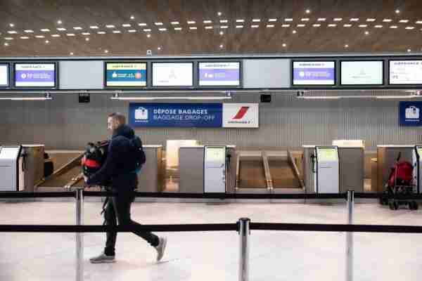 A traveler passes empty Air France-KLM baggage drop desks at Charles de Gaulle Airport, operated by Aeroports de Paris, in Roissy, France, on Thursday, March 12, 2020. President Donald Trumps 30-day ban on Europeans traveling to the U.S. delivers a hammer blow to a global airline industry that was already at risk of losing as much as $113 billion in passenger revenue this year because of the coronavirus. Photographer: Christophe Morin/Bloomberg via Getty Images