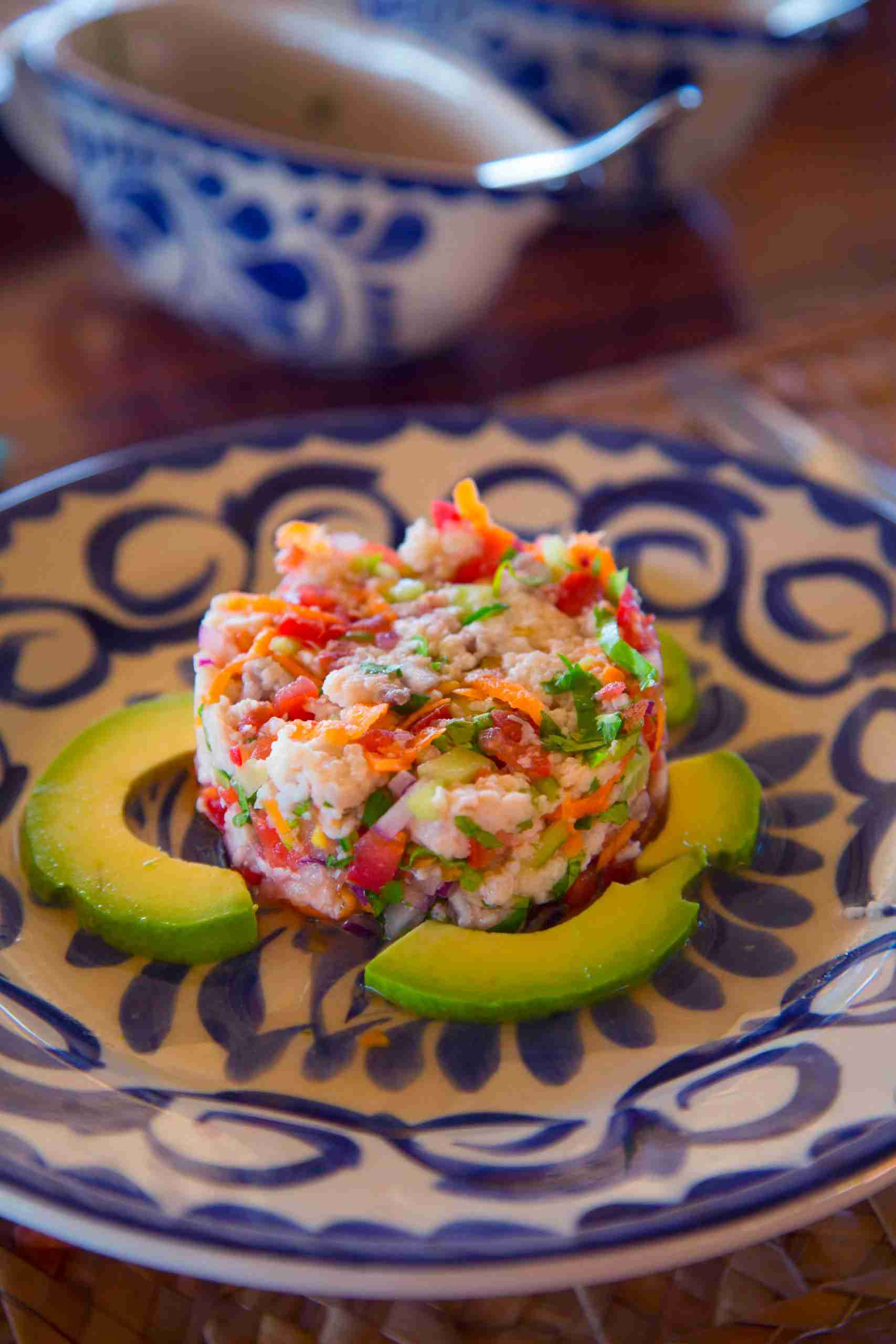 Ceviche is a seafood dish popular in the coastal regions of the Americas, especially Central and South America. The dish is typically made from fresh raw fish marinated in citrus juices, such as lemon or lime, and spiced with aji or chili peppers. Additional seasonings, such as chopped onions, salt, and coriander, may also be added. Ceviche is usually accompanied by side dishes that complement its flavors, such as sweet potato, lettuce, corn, avocado or plantain. As the dish is not cooked with heat, it must be prepared fresh to minimize the risk of food poisoning.
