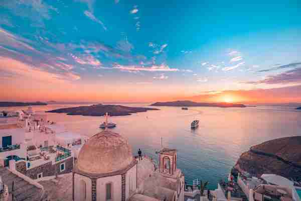 Amazing evening landscape of Fira, infinity pool caldera view Santorini, Greece with cruise ships at sunset. Cloudy dramatic sky sunset, wonderful summer scenery, travel vacation, holiday. Inspire. Photo by Levente Bodo/Getty Images