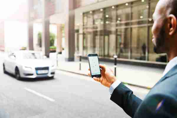 Businessman using taxi app. This is not a real branded app. The app is a mock-up featuring a map with car/taxi icons on it. Photo by Tim Robberts/Getty Images.