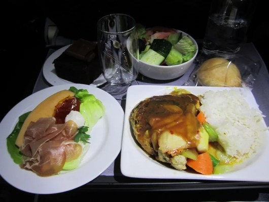 Our meal aboard the Boeing 787 included roasted chicken, prosciutto and melon, and chocolate cake.